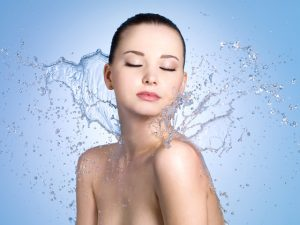 Beautiful portrait of woman with fresh skin in splashes of water - blue background