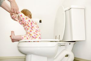 Baby girl (12-15 months) sitting on toilet, holding mother's hands